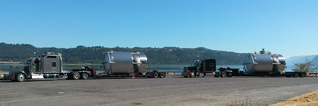 2 trucks hauling large cylinders